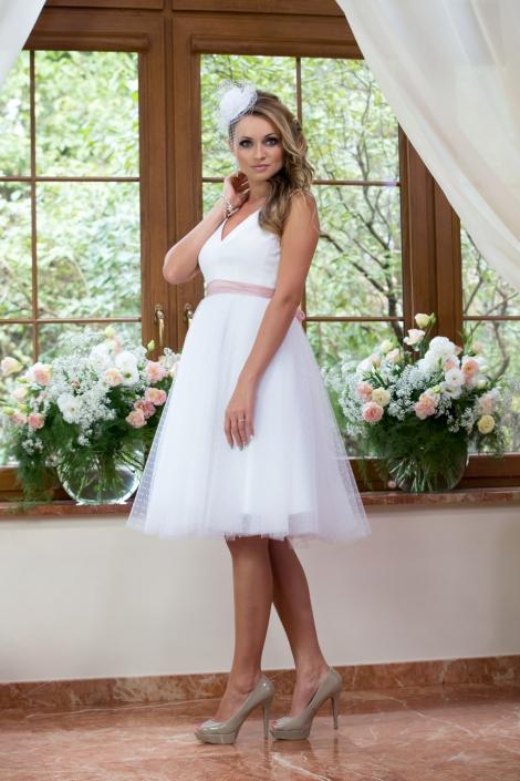 Sesja zdjęciowa - modelka w ślubnej sukni. Suknia ślubna do kolan biały tiul w kropeczki w talii szarfa