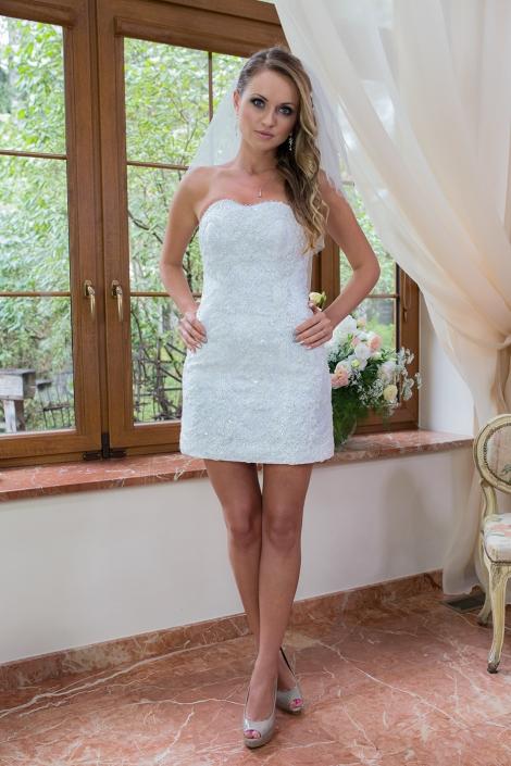 Sesja fotograficzna - suknia ślubna na modelce we wnętrzu. Koronkowa połyskliwa dopasowana suknia ślubna mini