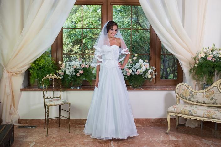 Sesja zdjęciowa - suknia ślubna na modelce we wnętrzu. Suknia ślubna bez ramiączek, gorset z koronki, atłasowy paseczek w talii