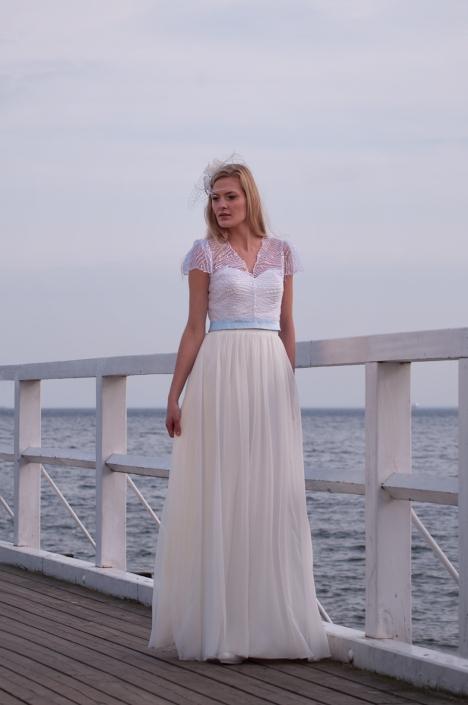 Sesja zdjęciowa - na modelce, suknia ślubna, zdjęcie na nadmorskim molo. Suknia ślubna z błyszczącą satynową dopasowaną narzutką