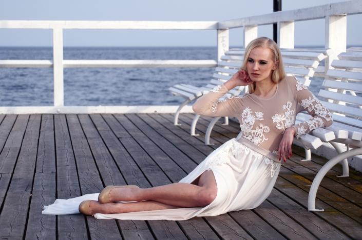 Sesja zdjęciowa - na modelce, suknia ślubna, zdjęcie na nadmorskim molo. Długa suknia z dopasowanym cielistym topem wyszywanym koronką i głębokim rozporkiem w spódnicy