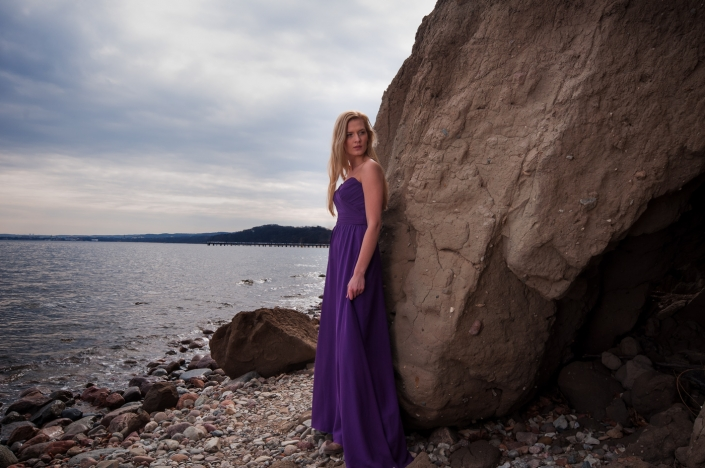 Sesja zdjęciowa - suknia wieczorowa na modelce, zdjęcie na plaży. Fioletowa suknia wieczorowa z drapowanym gorsetem i odkrytymi ramionami