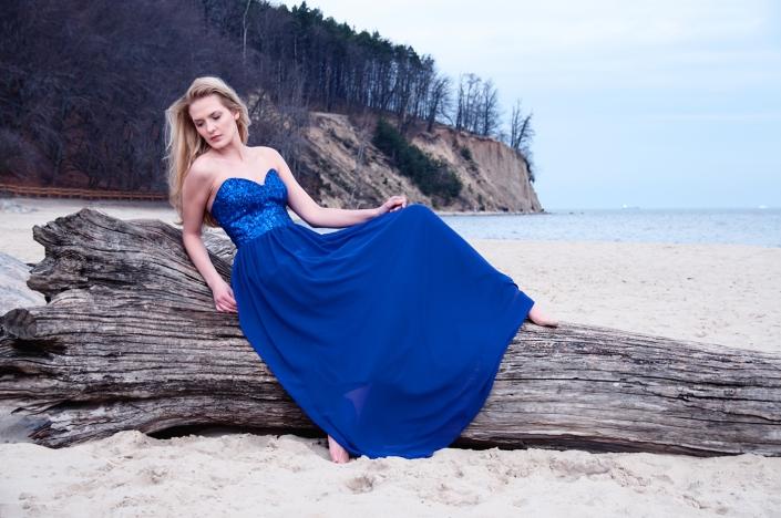 Sesja zdjęciowa - suknia wieczorowa na modelce, zdjęcie na plaży. Granatowa suknia wieczorowa cekinowy gorset