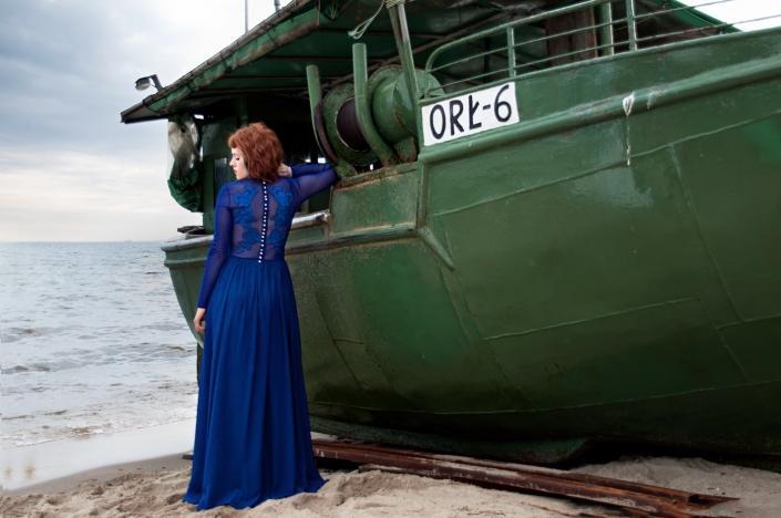 Sesja zdjęciowa - suknia wieczorowa na modelce, zdjęcie w porcie. Granatowa suknia wieczorowa z koronkową aplikacją na plecach