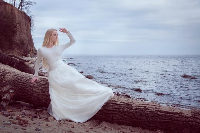 Sesja fotograficzna plenerowa- modelka w sukni ślubnej na plaży, biały komplet ślubny, top z długą spódnicą z szerokim satynowym paskiem