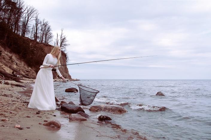 Sesja fotograficzna - modelka w sukni ślubnej na plaży