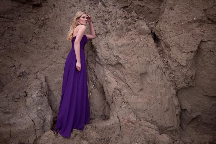 Sesja fotograficzna fioletowa suknia wieczorowa z drapowanym gorsetem i odkrytymi ramionami